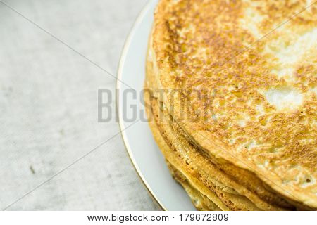 Stack of delicious golden crepes on white plate on linen cloth background top view breakfast