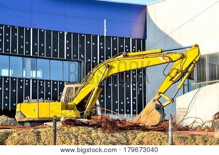 Excavator on a construction site. Yellow excavator at the construction of a new swimming pool in the city.