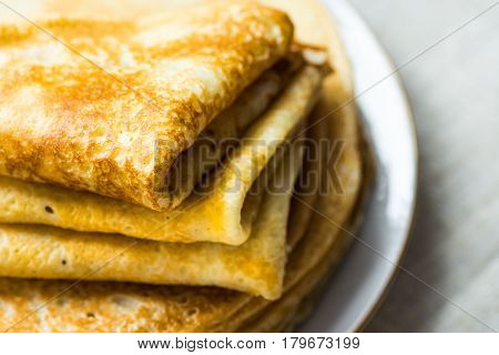Stacked folded crepes on white plate on linen cloth background closeup breakfast cozy morning atmosphere