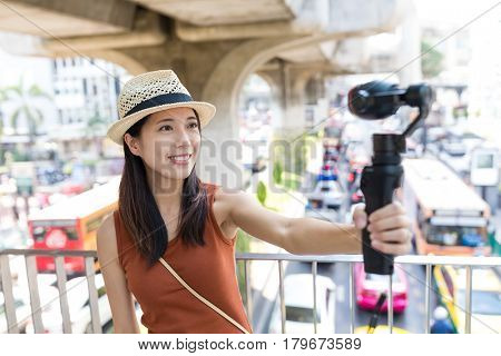 Woman using video camera for taking video in Bangkok city