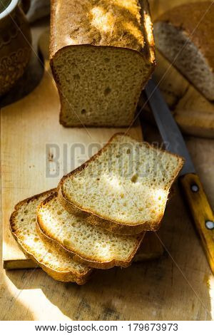 Loaf of sourdough bread cut into slices on wood cutting board knife kitchen table sunlight flecks cozy morning atmosphere
