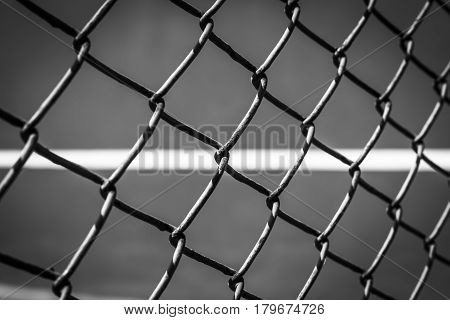Close-up wire mesh steel with cort tennis background in black and white.