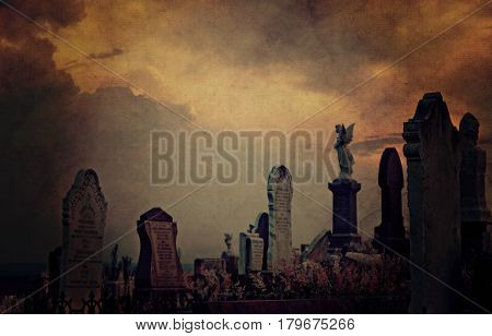 Gothic cemetery landscape at twilight with old headstones and angels under a dramatic sky. Vintage grunge textured and toned image.