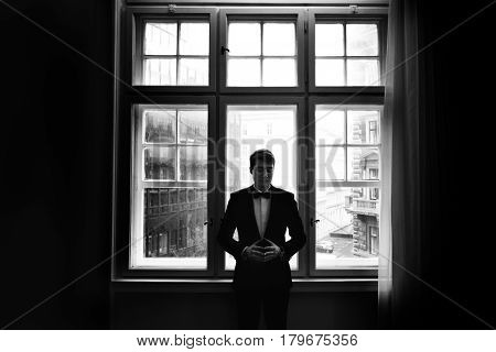 Man in a tuxedo stands thoughtful in the front of a bright window