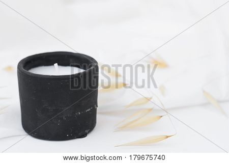 Black stone candle dry plants wild oats on white background styled stock image for social media marketing blogging