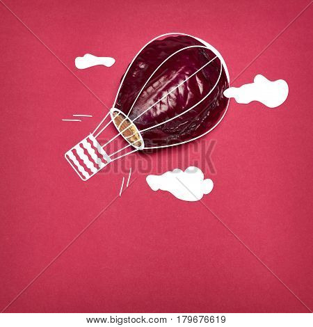 The pop art collage of red cabbage as aerostat on red background
