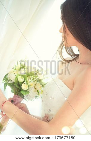 Beauty fashion Young model Bride in wedding white dress holding bouquet, looking out the window. Wedding. Dress salon. Beautiful fiancee in elegant white wedding dress, perfect makeup and hairstyle