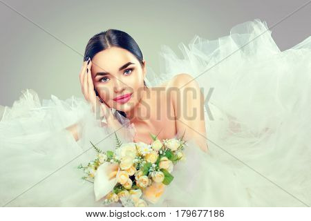 Beauty fashion Young model Bride in wedding dress with long train holding bouquet, posing in studio. Wedding Dress salon. Beautiful fiancee in elegant white wedding dress, perfect makeup and hairstyle