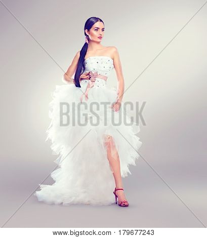 Beauty fashion Young model Bride in wedding dress with long train posing in studio. Wedding Dress salon. Beautiful fiancee in elegant white wedding dress, perfect makeup and hairstyle. Full length
