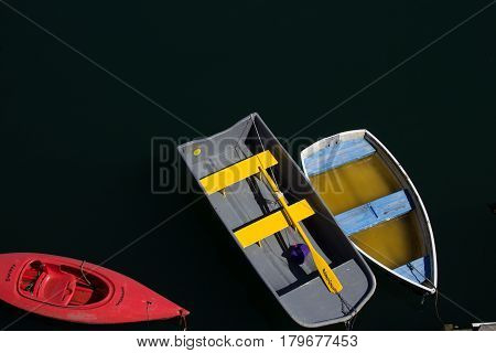 Grey and blue rowboats next to a red kayak floating on water moored to dock