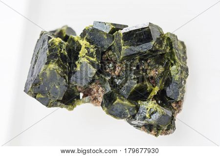 Druse of green epidote crystals on white background