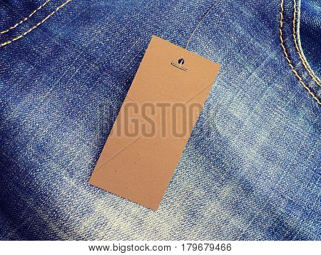 Label price tag mockup on blue jeans from recycled paper. Mock-up for price or brand presentation.