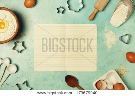 Baking background with flour, eggs, kitchen tools and recipe book on blue rustic table. Top view. Flat lay style.