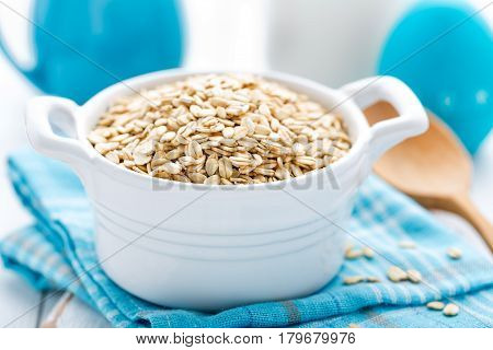 Rolled oats on white wooden background closeup