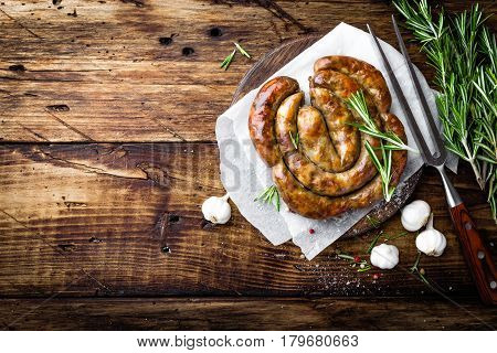 Grilled sausage on dark rustic wooden background top view