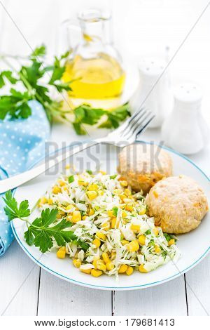 Vegetable cabbage salad and meatballs on plate close up white background