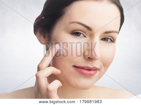 Digital composite of Woman with cream on face against white wall