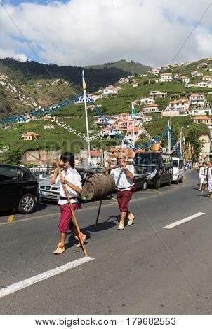 ESTREITO DE CAMARA DE LOBOS PORTUGAL - SEPTEMBER 10 2016: Men wearing in traditional costumes carry wine barrel at Madeira Wine Festival in Estreito de Camara de Lobos Madeira Portugal. The Madeira Wine Festival honors the grape harvest with a celebration