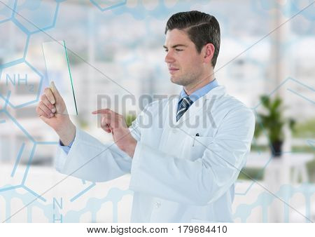 Digital composite of Man in lab coat holding up glass device against blue medical interface and blurry office