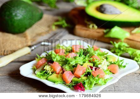 Salmon, avocado and mixed lettuce salad. Quick salad with salmon slices, fresh avocado and lettuce leaves mix on a plate. Avocado and half, fork on a vintage wooden table. Closeup