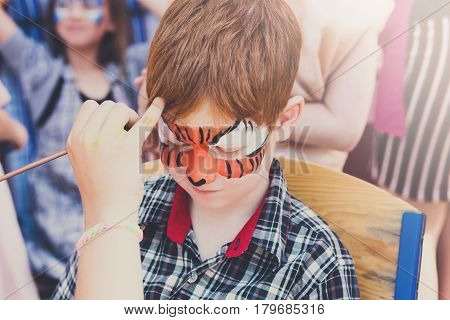 Child animator, artist's hand draws face painting to little boy. Kid with funny face art, tiger eyes