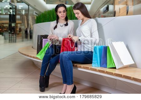 Two Cute Girls Are Sitting On A Bench In The Mall With Gift Bags Looking Inwards.