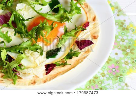 Flour tortilla with fried egg, hummus and fresh salad mix on a plate. High protein vegetarian tortilla photo. Healthy breakfast or lunch recipe. Closeup