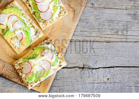 Hearty and quick veggie cracker with sauce and vegetables. Sliced avocado and radishes on crispy cracker with seeds on wooden board and on a vintage wooden background with copy space. Top view