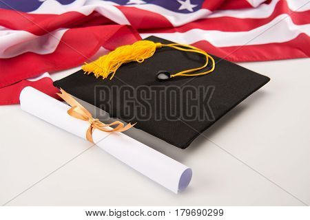 Close-up view of graduation mortarboard diploma and us flag on grey education concept
