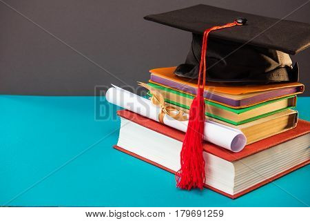 book diploma and graduation cap with tassel on blue with copy space education concept