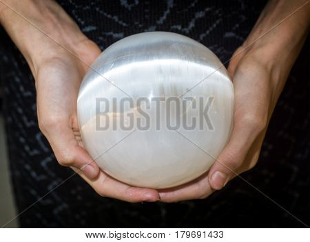 Close up shot of crop female hands holding sphere made of selenite or white quartz.