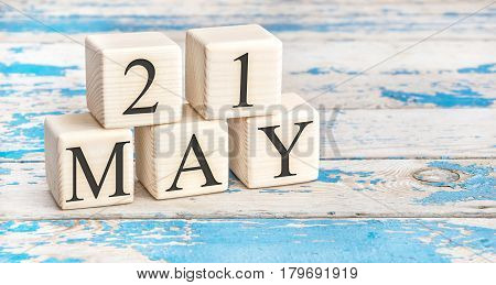 May 21st. Wooden cubes with date of 21 May on old blue wooden background.