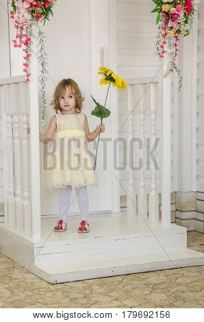 little cute girl in a yellow dress with a sunflower is standing near the door