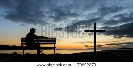 A man on a seat next to a cross at Foxton Beach river.