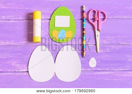 Creating Easter egg greeting card. Step. Colored paper greeting card with eggs, templates in shape of egg, scissors, glue stick, pencil on a wooden table. Easy Easter craft idea for children. Top view