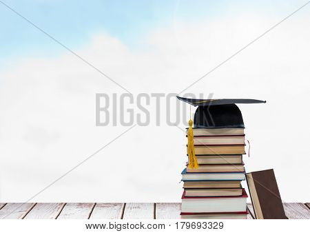 Digital composite of Books stacked by blue sky