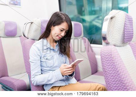 Young Woman using mobile phone on train compartment