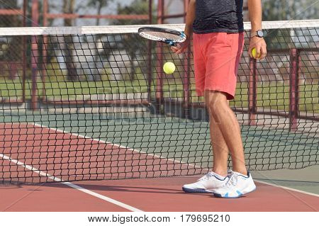 Male tennis player with racket ready to serve a tennis ball. Healthy fitness concept with active lifestyle