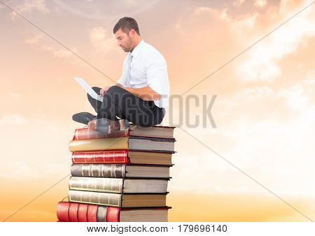 Digital composite of Businessman sitting on Books stacked by sunset with laptop