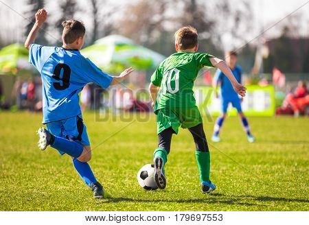 Kids kicking soccer ball on vivid green grass field. Soccer pitch in the background. Football soccer background. Football league game