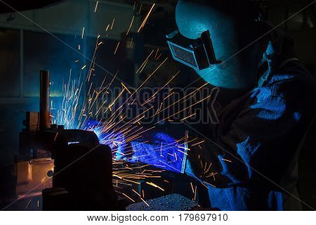 worker welding automotive part in car factory