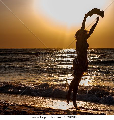 An attractive girl runs happily out of the sunlit sea