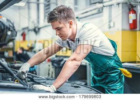 Young mechanic in hood of car