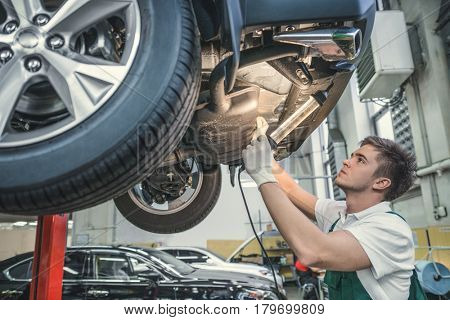Young mechanic with car