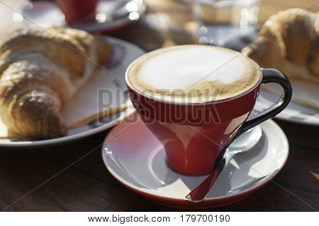Coffee cup of cappuccino with croissant on wooden table.