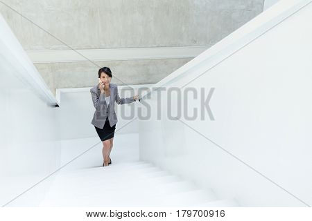 Business woman talk to mobile phone and walking upstairs
