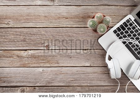 Headphones over laptop on wooden desk table. Music concept. Top view with copy space