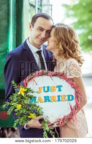 Close up portrait of loving couple. Man and woman standing near the wagon with a sign just married in Lviv Ukraine