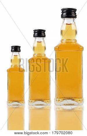 Different size Whisky bottles on white background