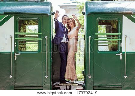 Just married couple standing at the junction between by wagons in Lviv, Ukraine